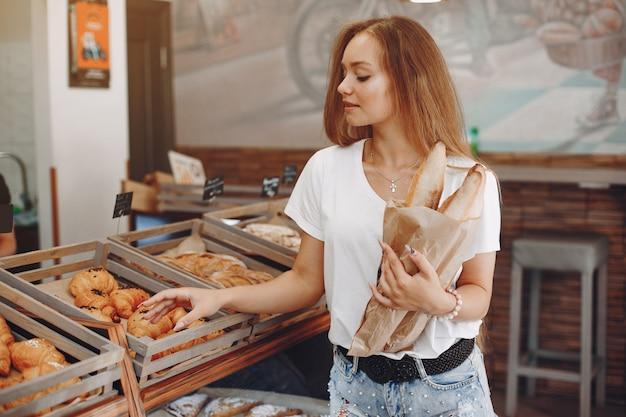 Linda garota compra pães na padaria