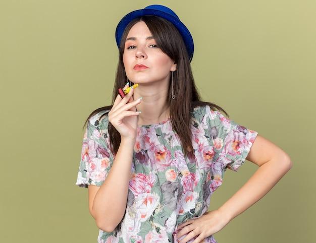Linda garota confiante com um chapéu de festa, segurando o apito de festa e colocando a mão no quadril