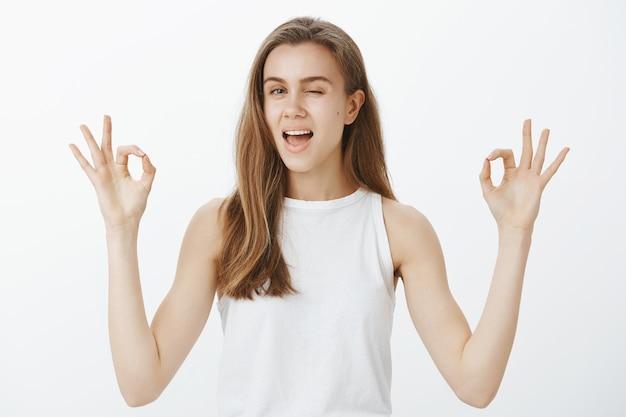 Linda garota confiante e atrevida garante tudo bem, mostrando gestos bem e piscando para tranquilizar