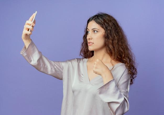 Linda garota confiante tirando uma selfie e segurando o punho isolado na parede azul