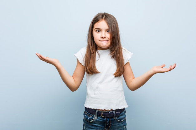 Linda garota confusa e duvidosa, levantando as mãos para segurar um espaço de cópia.