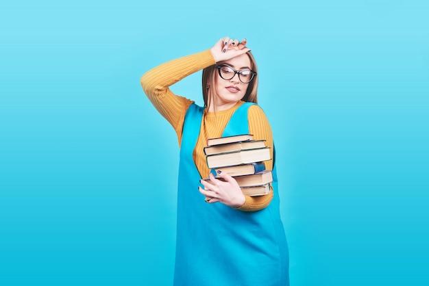 Linda garota confusa, segurando nas mãos uma pilha de livros isolados em azul colorido