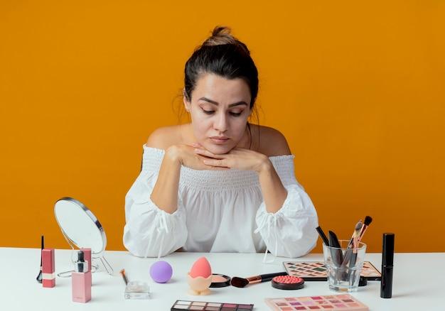 Linda garota confusa sentada à mesa com ferramentas de maquiagem coloca as mãos no queixo olhando para baixo isolado na parede laranja
