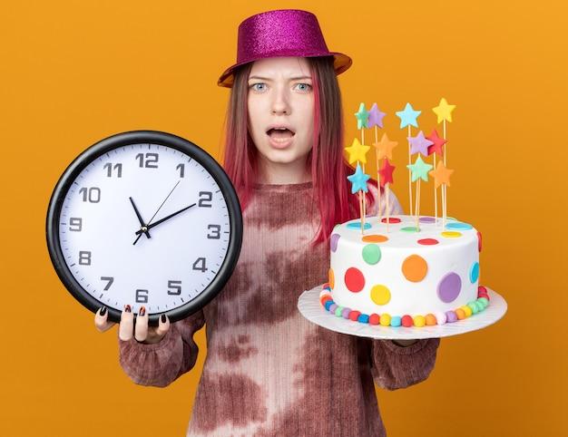 Linda garota confusa usando um chapéu de festa segurando um bolo com um relógio de parede isolado na parede laranja