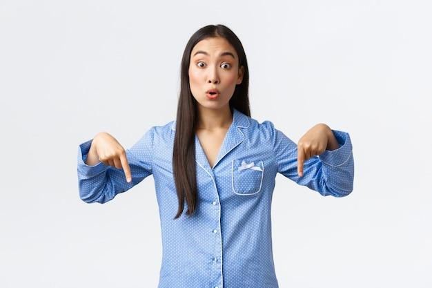 Linda garota coreana surpresa e curiosa de pijama azul fazendo perguntas