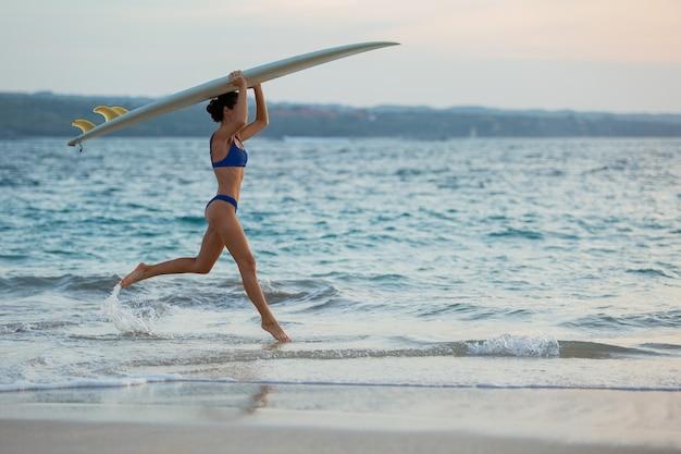 Linda garota corre ao longo da praia com uma prancha de surf.