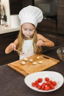 Linda garota cortando fatias de ovo na tábua de cortar com faca