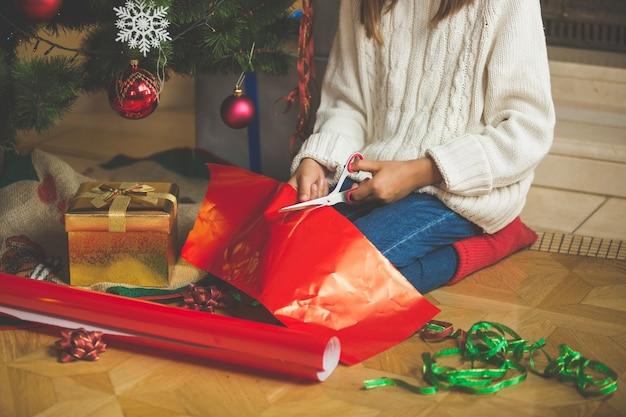 Linda garota cortando papel de embrulho embaixo da árvore de natal na sala de estar