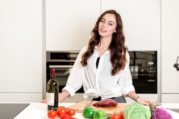 Linda garota cozinhar carne na cozinha com legumes