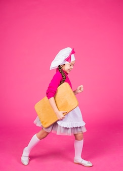 Linda garota cozinhar vai com placa de madeira