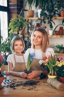 Linda garota criança ajuda a mãe a cuidar das plantas. a mãe e a filha dela dedicam-se à jardinagem. família feliz na primavera.