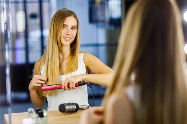 Linda garota cuidando do cabelo com ferros