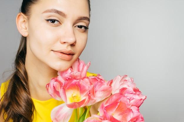 Linda garota curtindo a primavera, segurando um grande buquê de flores cor de rosa