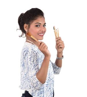 Linda garota curtindo com pincéis de maquiagem isolados no branco