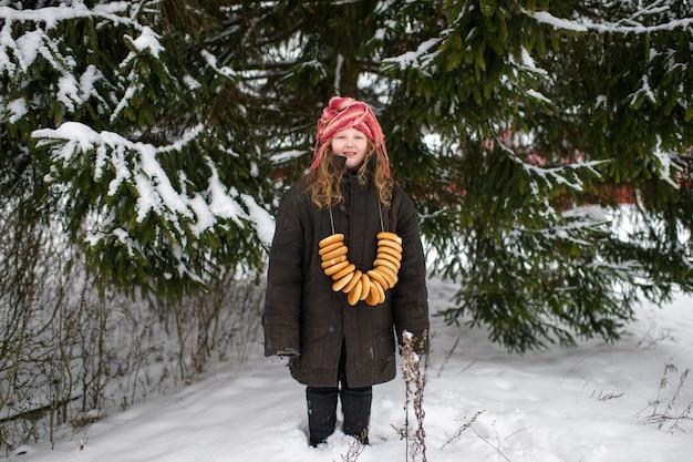 Linda garota da aldeia fica em uma floresta de neve com rolos secos em forma de anel e sorrisos no inverno