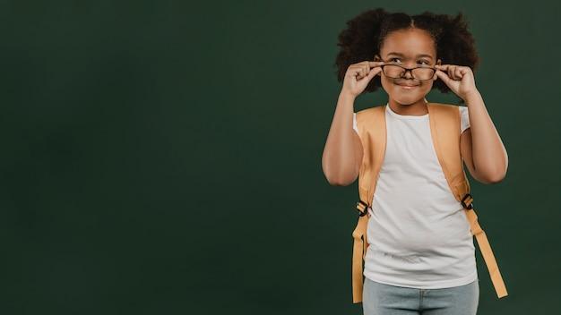 Linda garota da escola arrumando seus óculos de leitura