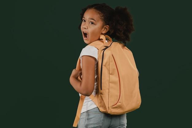 Linda garota da escola e sua mochila vista de trás