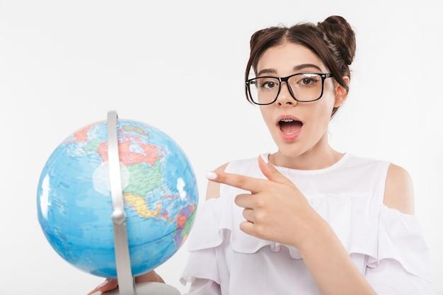 Linda garota da escola inteligente com penteado de pãezinhos duplos e aparelho dentário usando óculos apontando o dedo para o globo terrestre, isolado no branco