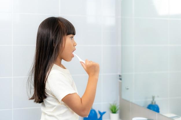 Linda garota da escola primária, escovando os dentes e olhando no espelho no banheiro em casa.