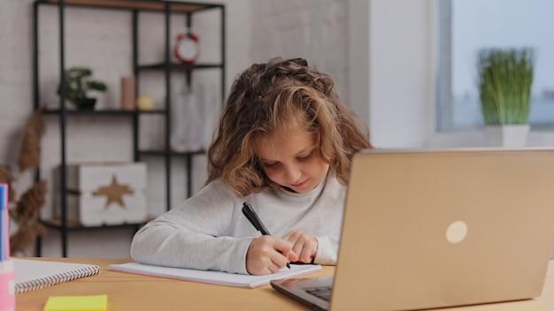 Linda garota da escola primária, estudando em casa, usando o computador portátil. aluna tem aula online, escrevendo no livro de exercícios, fazendo lição de casa.