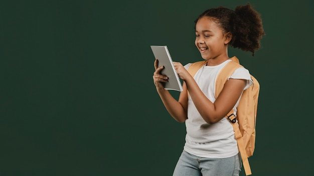Linda garota da escola usando um tablet digital