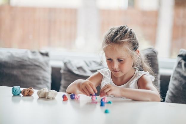 Linda garota da pré-escola jogando jogos educativos com bonecos de plasticina se preparando para a escola no jardim de infância