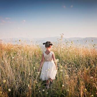 Linda garota dançando através de um belo prado com trigo e flores nas montanhas, vista traseira