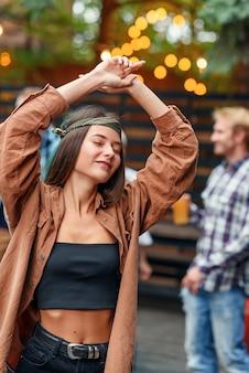 Linda garota dançando em primeiro plano, enquanto seus amigos dançando à luz de lâmpadas coloridas durante a festa de comemoração ao ar livre.