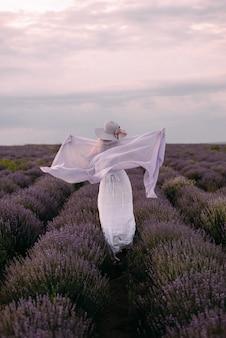 Linda garota dançando no campo de lavanda, correndo no prado de flores roxas