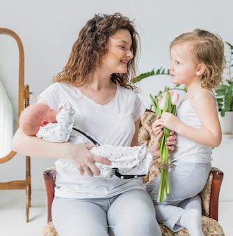 Linda garota dando flores tulipa para a mãe dela segurando bebê sentado na cadeira de braço