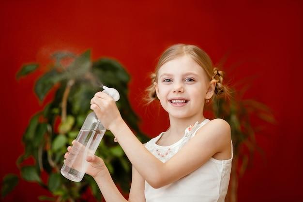 Linda garota de 7-8 anos de idade, cuidando de plantas domésticas, pulverizando água do pululador