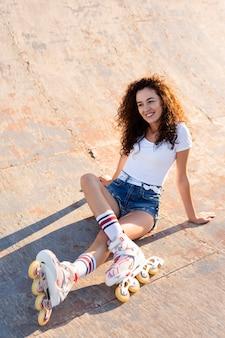 Linda garota de alto ângulo com cabelo encaracolado posando com seus patins