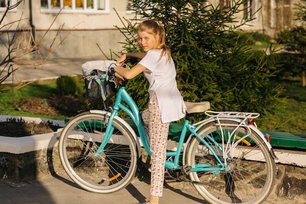 Linda garota de bicicleta azul. garota anda de bicicleta. férias de verão. gastar tempo com benefício. bicicleta feminina com cesta