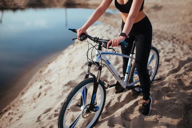 Linda garota de bicicleta na areia perto do rio