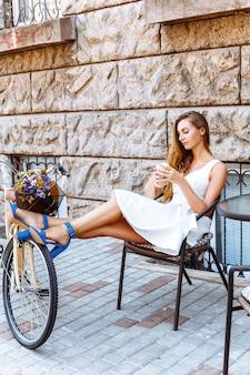 Linda garota de bicicleta perto de um prédio antigo
