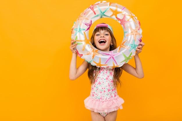 Linda garota de biquíni com um círculo de natação em uma parede amarela