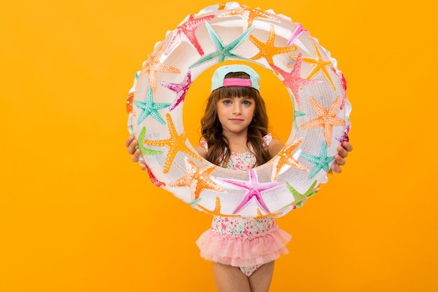 Linda garota de biquíni com um círculo de natação em uma parede laranja