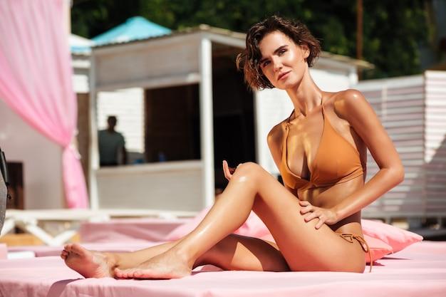 Linda garota de biquíni sentada na cama de praia e olhando pensativamente de lado.