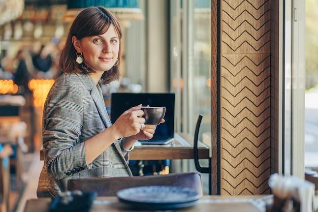 Linda garota de blazer cinza, bebendo café e trabalhando no netbook no café. freelancer, trabalhar numa cafetaria. aprendizagem online.