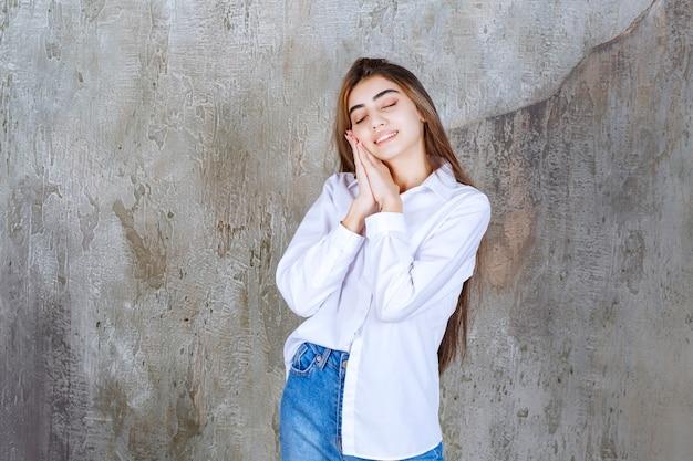 Linda garota de cabelo comprido com blusa branca em pé e dormindo