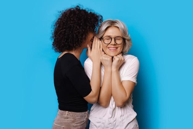 Linda garota de cabelo encaracolado sussurrando algo para sua garota loira posando em uma parede azul com os olhos fechados