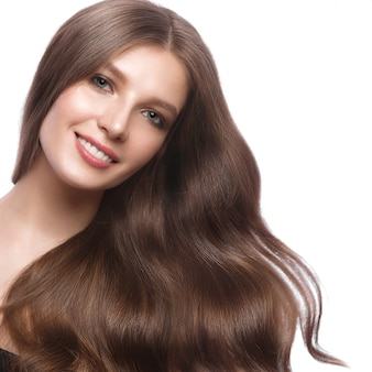 Linda garota de cabelos castanhos com cabelos perfeitamente cacheados e maquiagem clássica