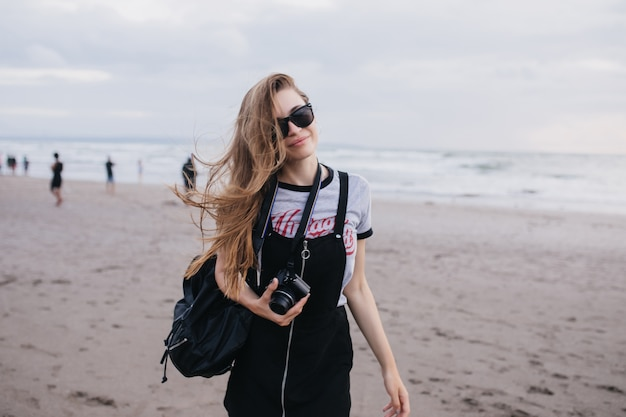 Linda garota de cabelos castanhos com câmera posando na natureza em dia nublado. foto ao ar livre da senhora bonita com mochila preta, caminhando pela praia.