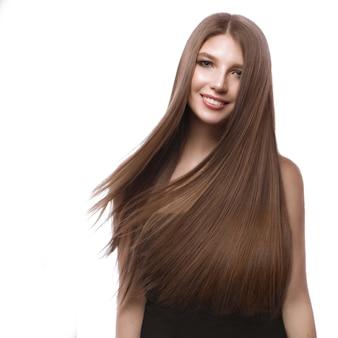 Linda garota de cabelos castanhos em movimento com um cabelo perfeitamente liso e maquiagem clássica.