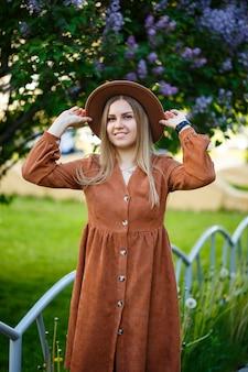 Linda garota de cabelos compridos bem torneada com chapéu em um fundo de flores lilás