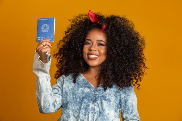Linda garota de cabelos crespos, segurando um cartão de trabalho. na parede amarela.