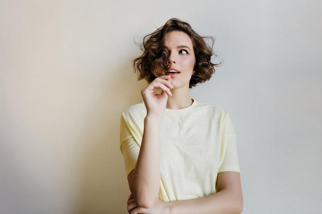 Linda garota de cabelos escuros com expressão de rosto pensativo posando. mulher atraente e encaracolada pensando em algo na parede branca.