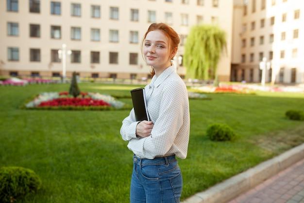 Linda garota de cabelos vermelha com sardas abraçando cadernos