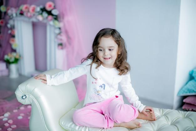 Linda garota de calça rosa senta-se em um sofá