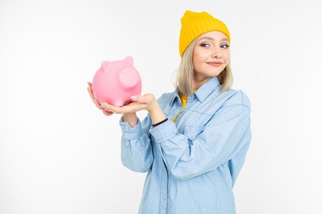 Linda garota de camisa azul com um banco para economizar dinheiro em um fundo branco, com espaço de cópia